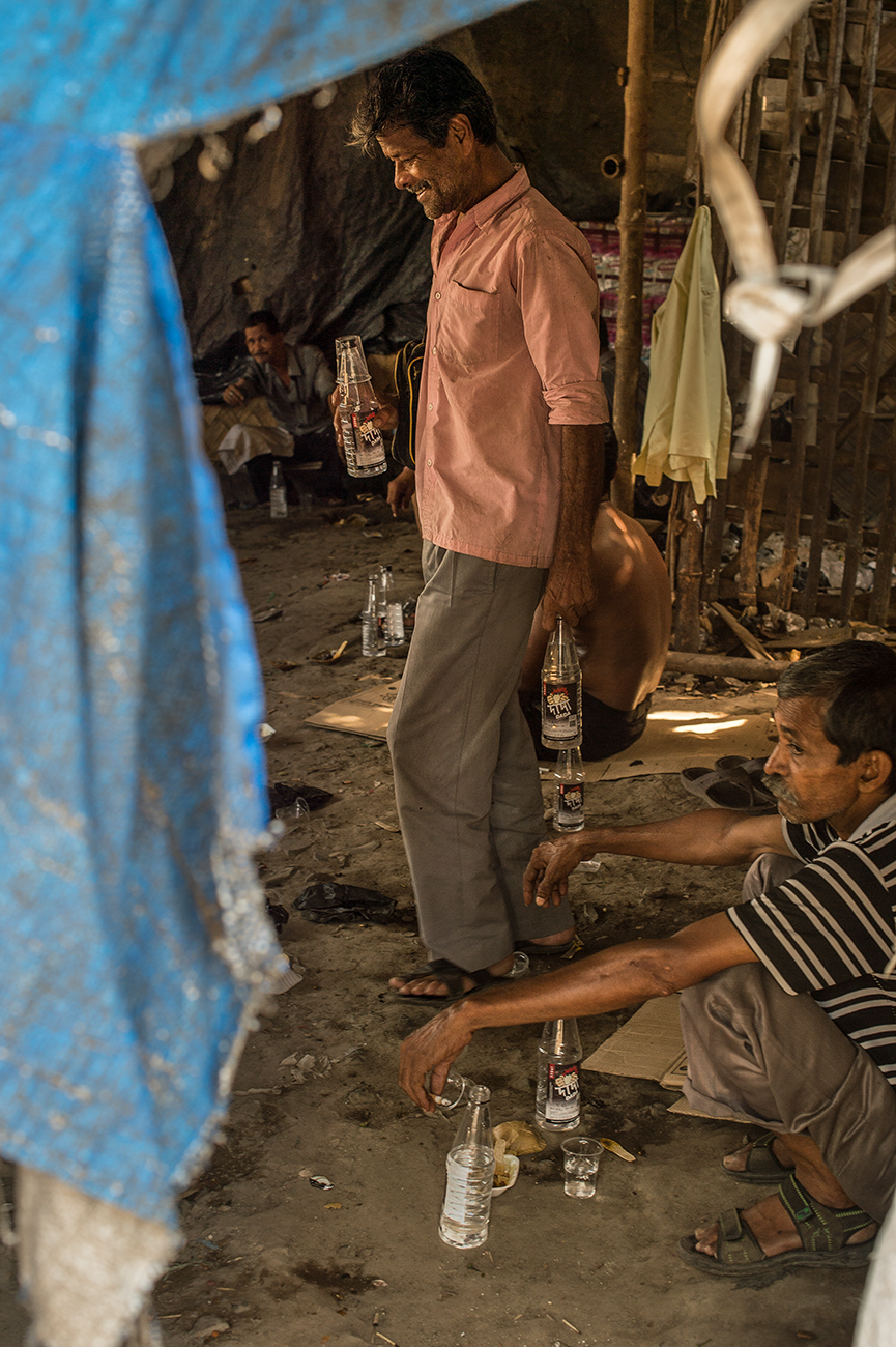 A drunk dalit workers in an illegal liquor store, near a tennery. Park Circus district.